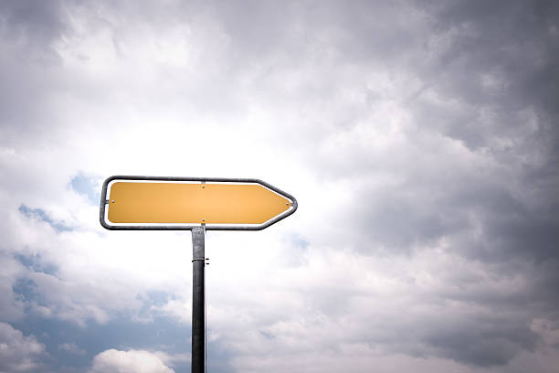 empty directional road sign with pointing arrow stock photo