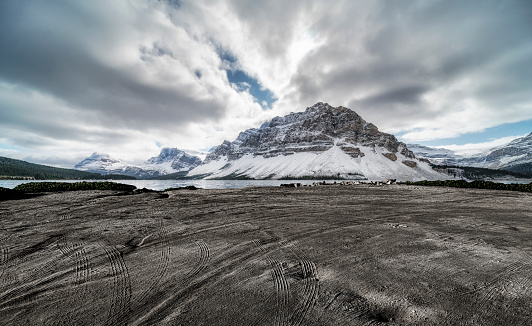 empty dirt beach with traces against Canadian Rockies, AB, Canada.