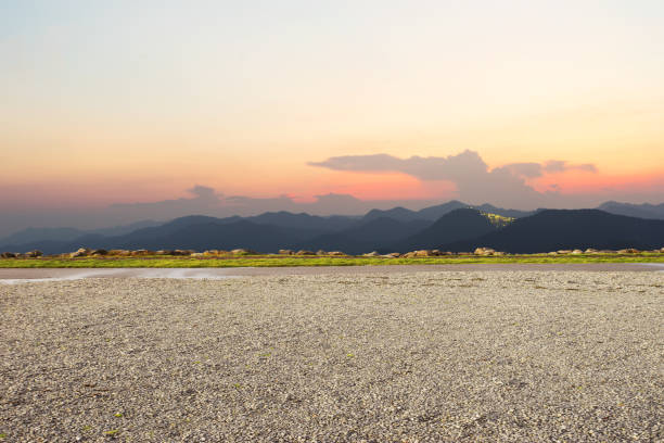 empty dirt floor with green mountains at twilight stock photo