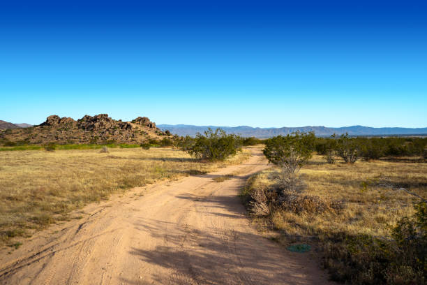 Empty dirt road with a rock hill formation in the Mojave Desert Town of Apple Valley stock photo