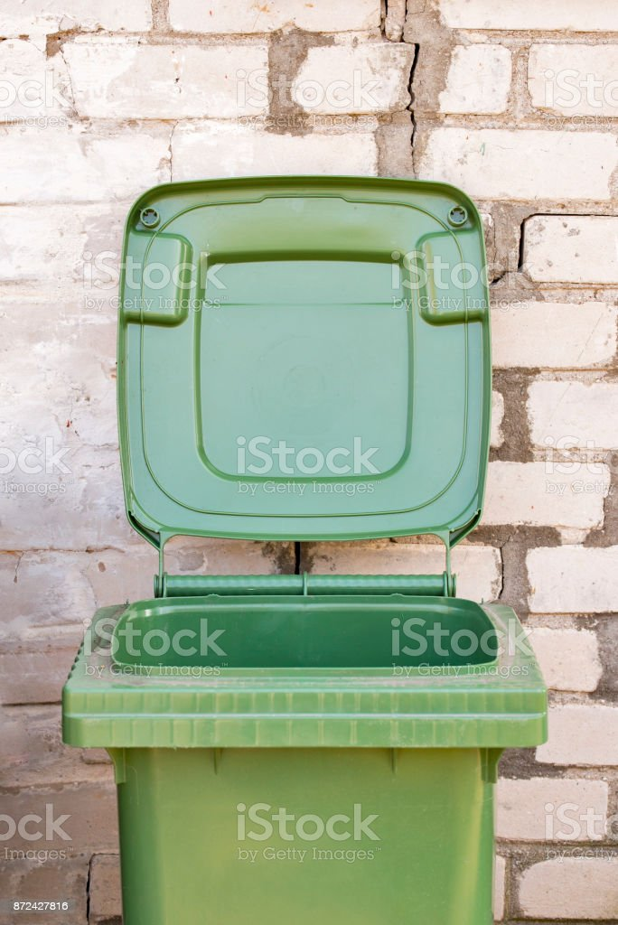 Empty dirty green recycle bin near the brick wall stock photo