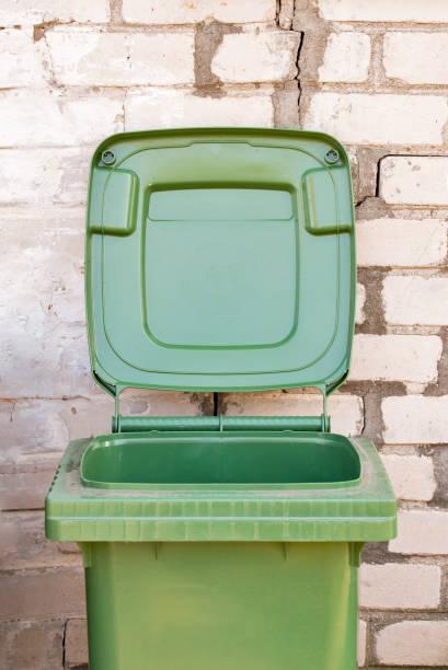 Empty dirty green recycle bin near the brick wall stock photo