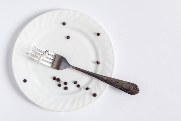 töm smutsig vit plåt och gaffel på den vita bakgrunden. smutsig tallrik med bitar och smulor dessert - tallrik uppätet bildbanksfoton och bilder
