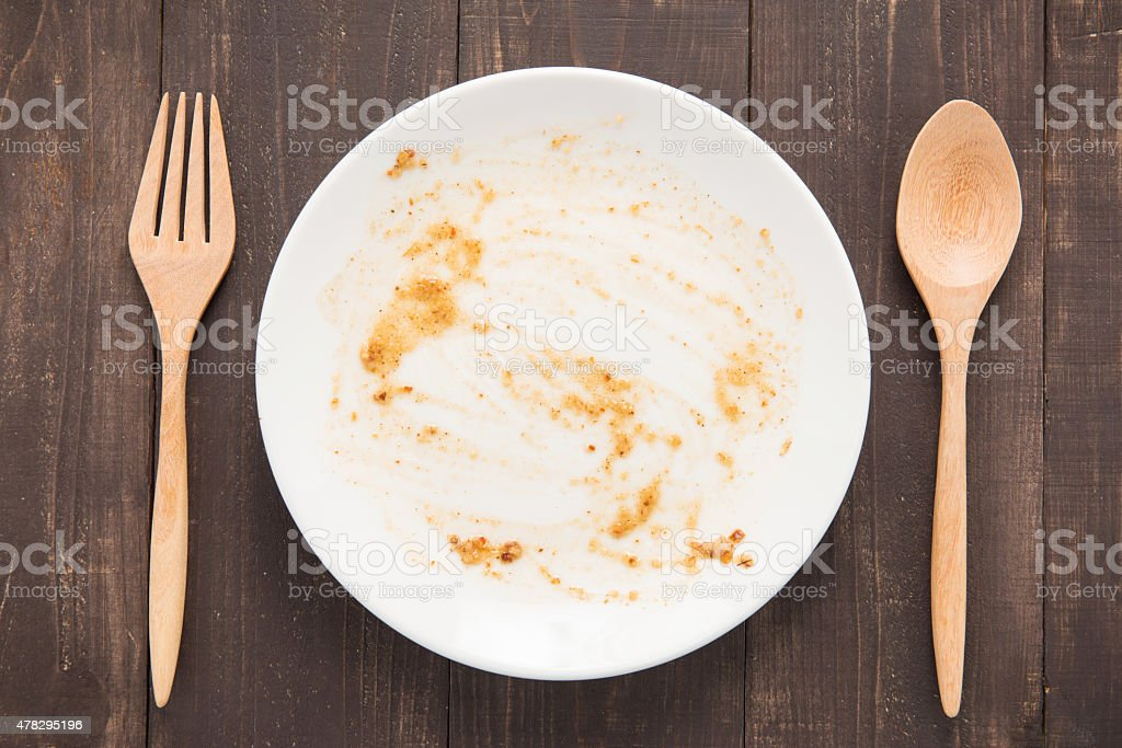 Empty dish after food on the wooden background stock photo
