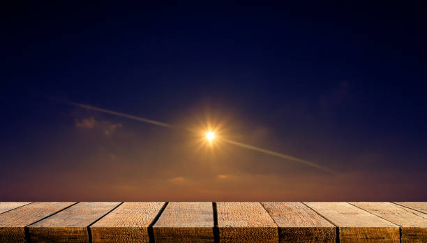 Contador de mesa de madera de la pantalla vacía para el telón de fondo de la publicidad y el fondo con la luz del sol brillante estrella en el cielo de la noche. - foto de stock