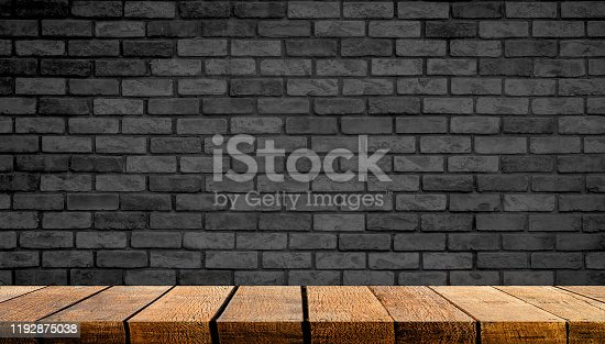 642100994istockphoto Empty display wooden board shelf table counter with copy space for advertising backdrop and background with Black brick wall in the background, 1192875038