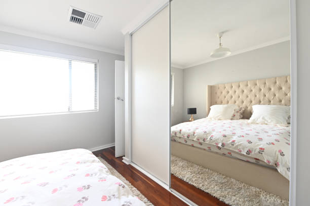 Empty double bed reflecting from a built-in wardrobe mirrow stock photo