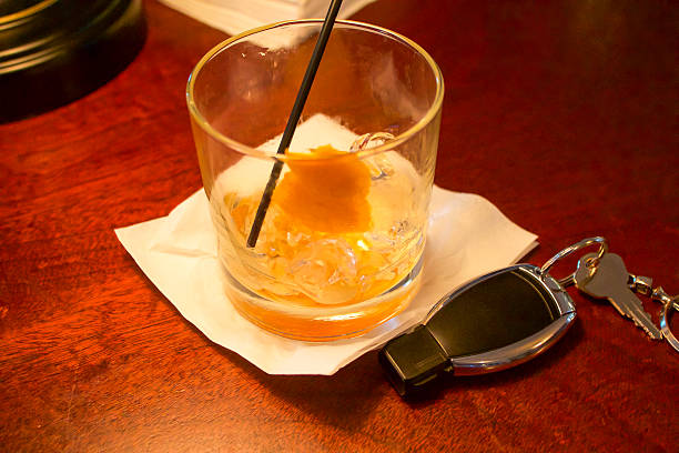 Empty Drink Next to Car Key on Wood Counter stock photo