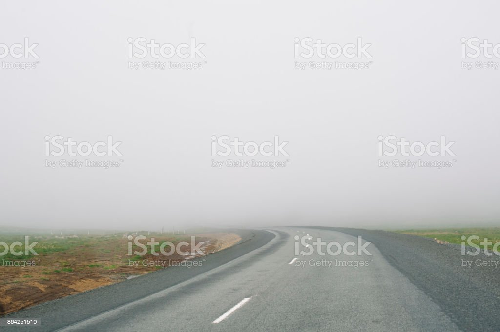 Empty driving road in Iceland with a dangerous dense fog royalty-free stock photo