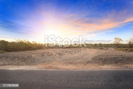 istock Empty dry cracked swamp reclamation soil, land plot for housing construction project with car tire print in rural area and beautiful blue sky with fresh air Land for sales landscape concept 1212925556