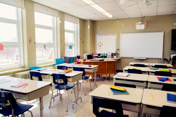 Empty elementary classroom during recess. Empty elementary classroom during recess. Interactive whiteboard at the side of teacher's desk. Horizontal indoors full length shot with copy space. elementary school stock pictures, royalty-free photos & images