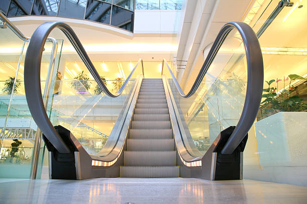 Empty escalator in a brightly lit shopping mall stock photo