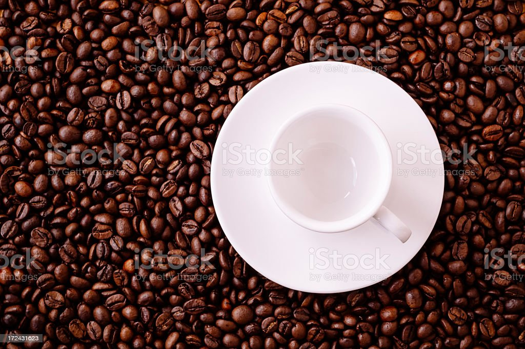 Empty espresso cup surrounded by coffee beans royalty-free stock photo