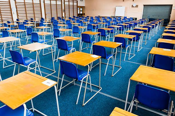 Empty exam desks set up in a school gym stock photo