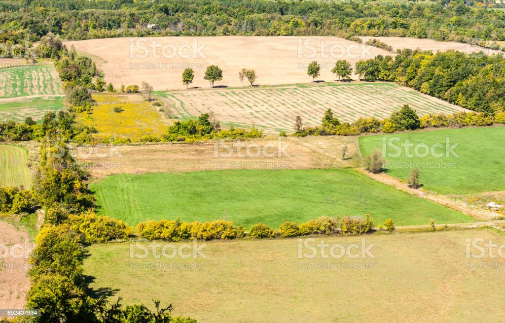 Empty farm fields bordered by tree lines. stock photo