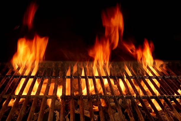 Empty Flaming Barbecue Grill Isolated On Black Background. stock photo
