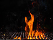 Empty flaming charcoal grill with open fire