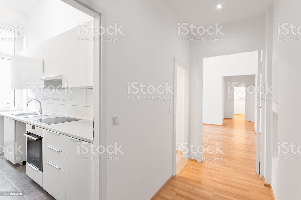 empty flat, white kitchen and wooden floor stock photo
