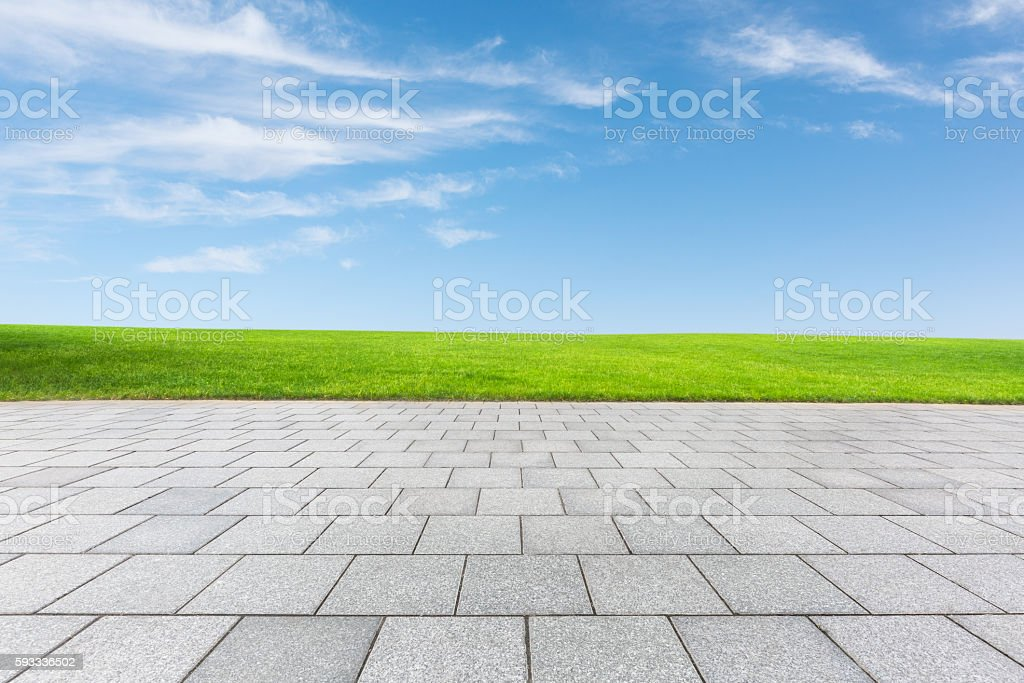 empty floor and green field under blue sky stock photo
