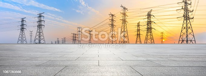Empty square floor and high voltage power towers at sunset