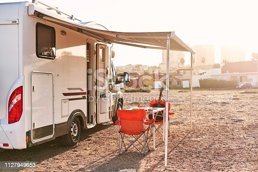 Empty folding chairs and table under canopy near recreational vehicle camper trailer. Adventure, active people traveling by motor home concept