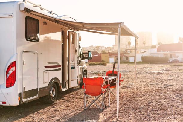 Leer, Klappstühle und Tisch unter Vordach in der Nähe von Freizeitfahrzeug Zeltanhänger, niemand – Foto