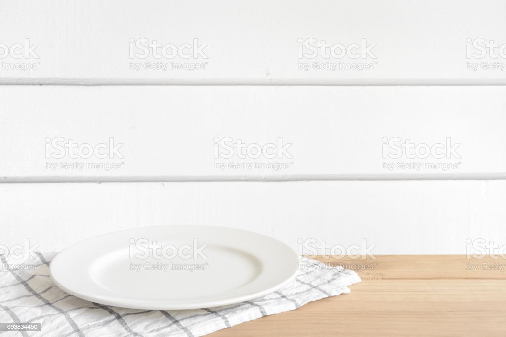 Empty white food plate put on wooden desk in white wood wall room.