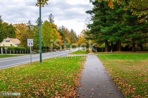 Empty path along a street on a cloudy autumn day. Stockbridge, MA, USA.