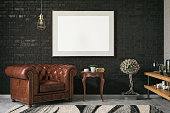 Black picture frame in living room with leather arm chair