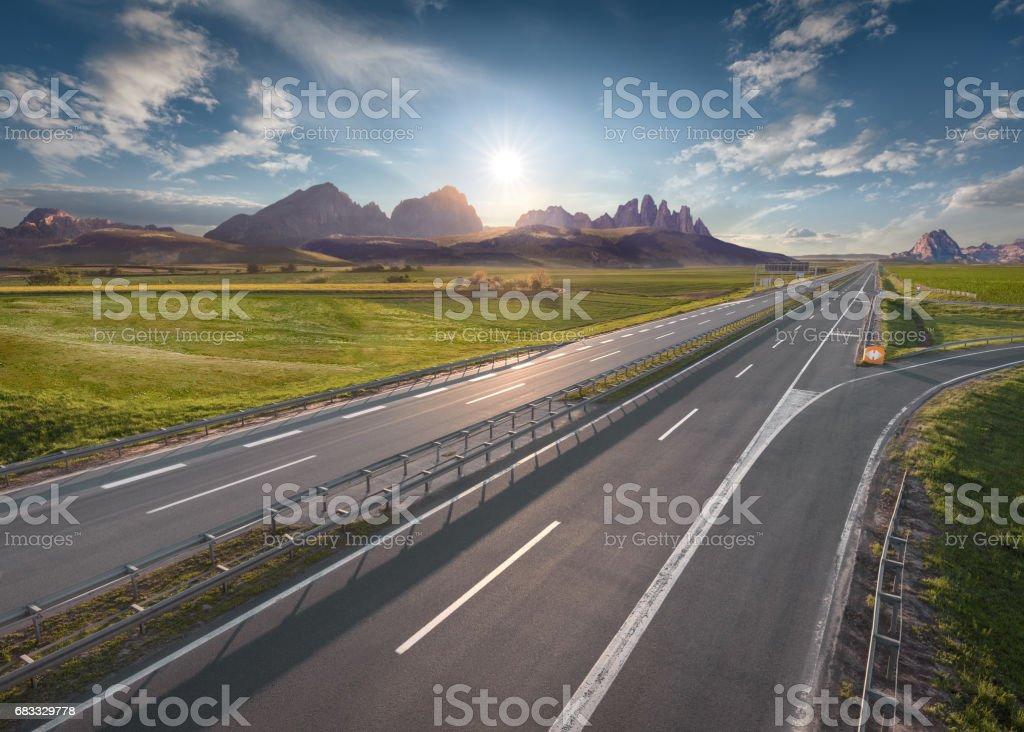 Empty freeway through vastness at idyllic sunrise royalty-free stock photo