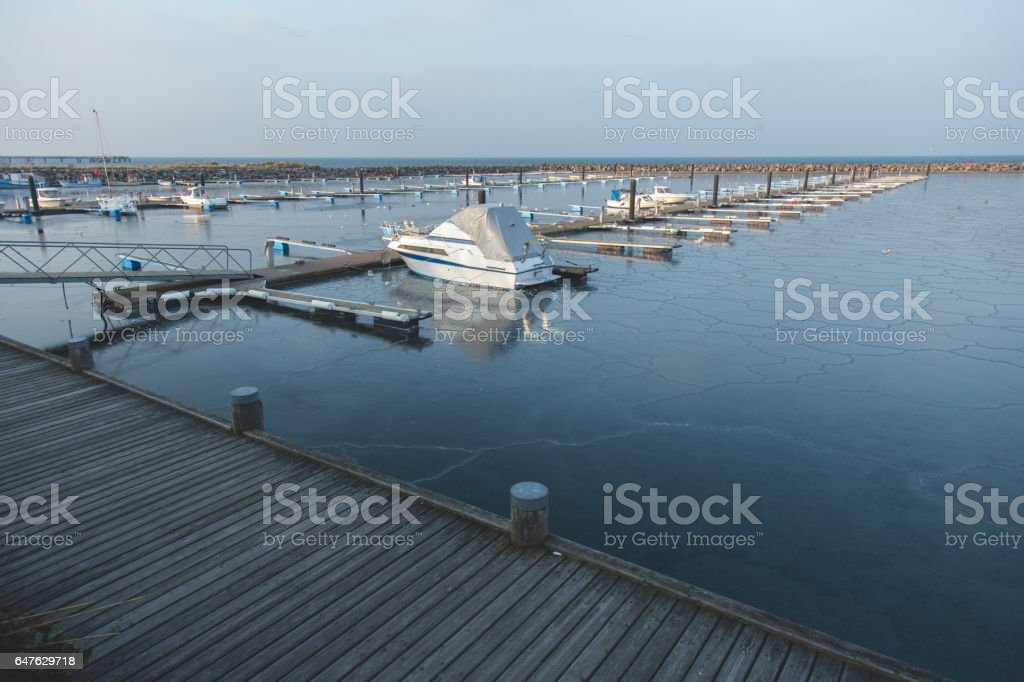 Empty frozen dock in sea with one boat parked stock photo