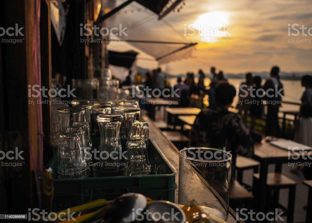 Leeg glas bij zonsondergang, op de tafel met ruimte voor de voorbereiding van het feest langs de Mekong rivier. zachte focus. foto