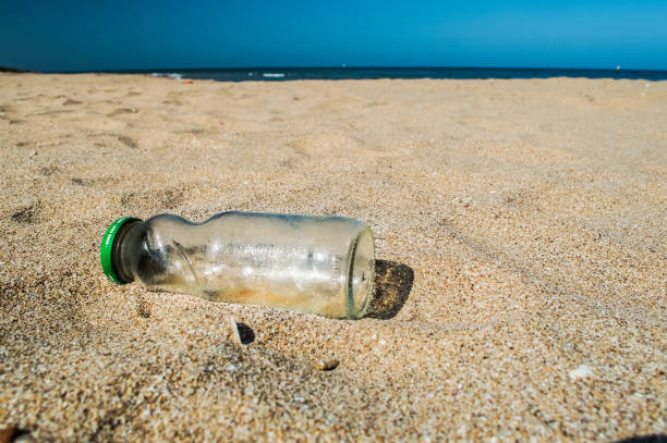Empty glass bottle garbage dumped on the beach stock photo