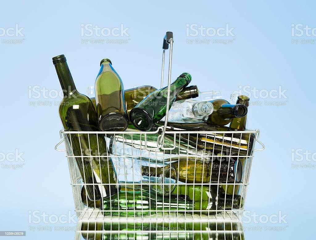 Empty glass bottles in a wastebasket stock photo