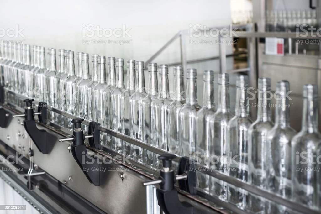 Empty glass bottles on the conveyor stock photo