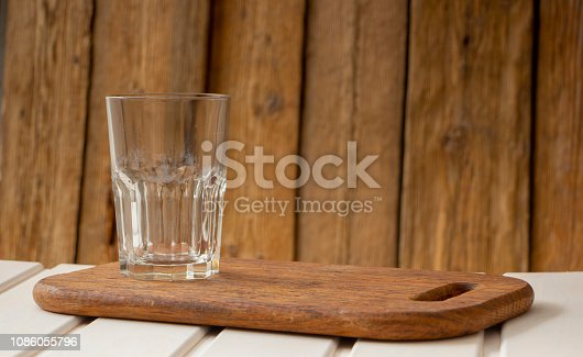 Empty glass cup on a wooden table, with space for writing text,