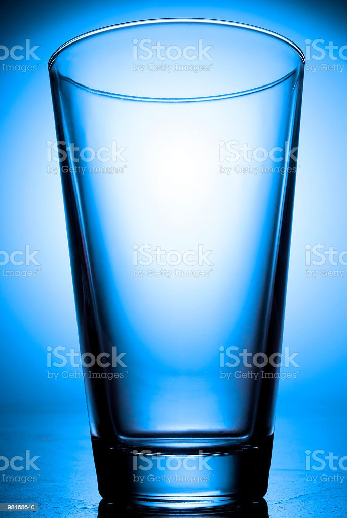 Empty glass on blue backlight. royalty-free stock photo