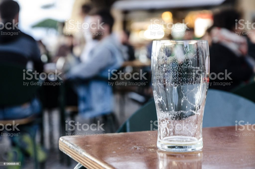 Empty glass with people drinking on public patio stock photo