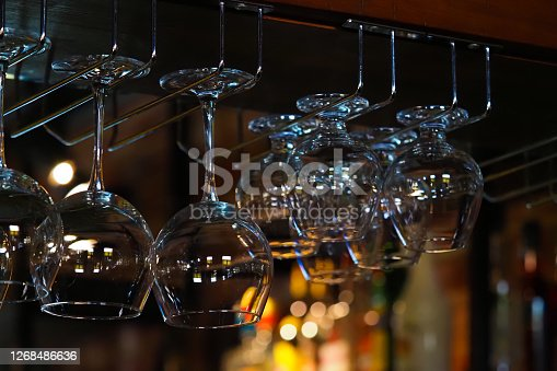 Empty glasses for wine above a bar rack. Hanging glasses in a restaurant