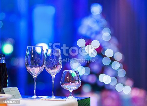 istock Empty glasses in restaurant with defocused Christmas tree 613650622