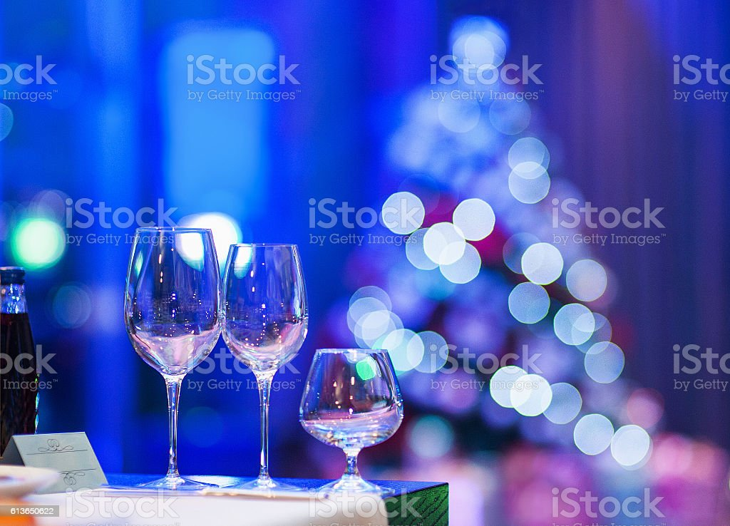 Empty glasses in restaurant with defocused Christmas tree stock photo