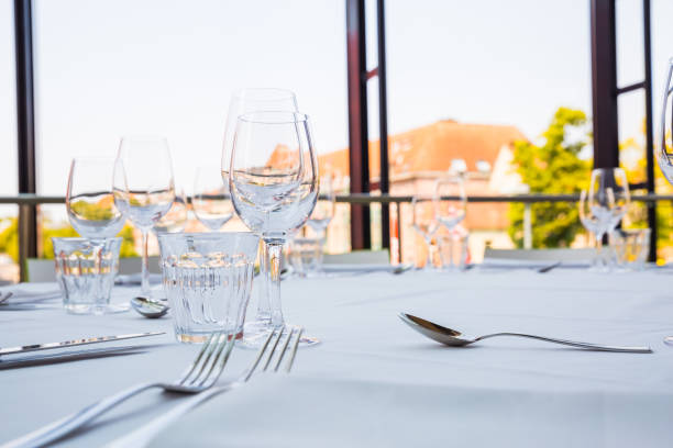 Empty glasses on a table covered with a white tablecloth in front of the panoramic window stock photo