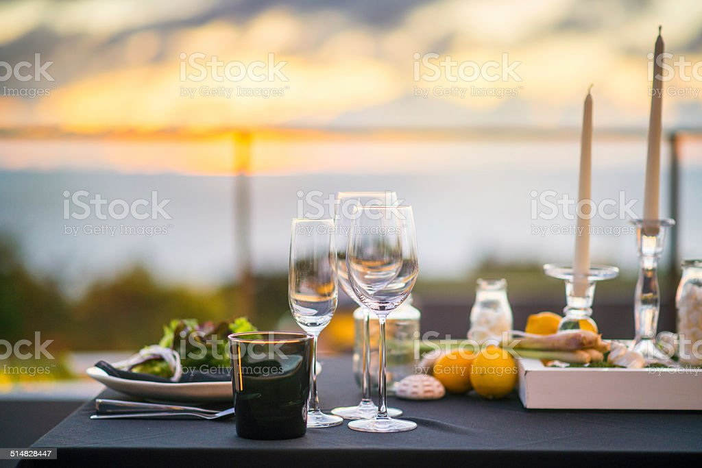 Empty glasses set in restaurant  Dinner table outdoors at sunset stock photo