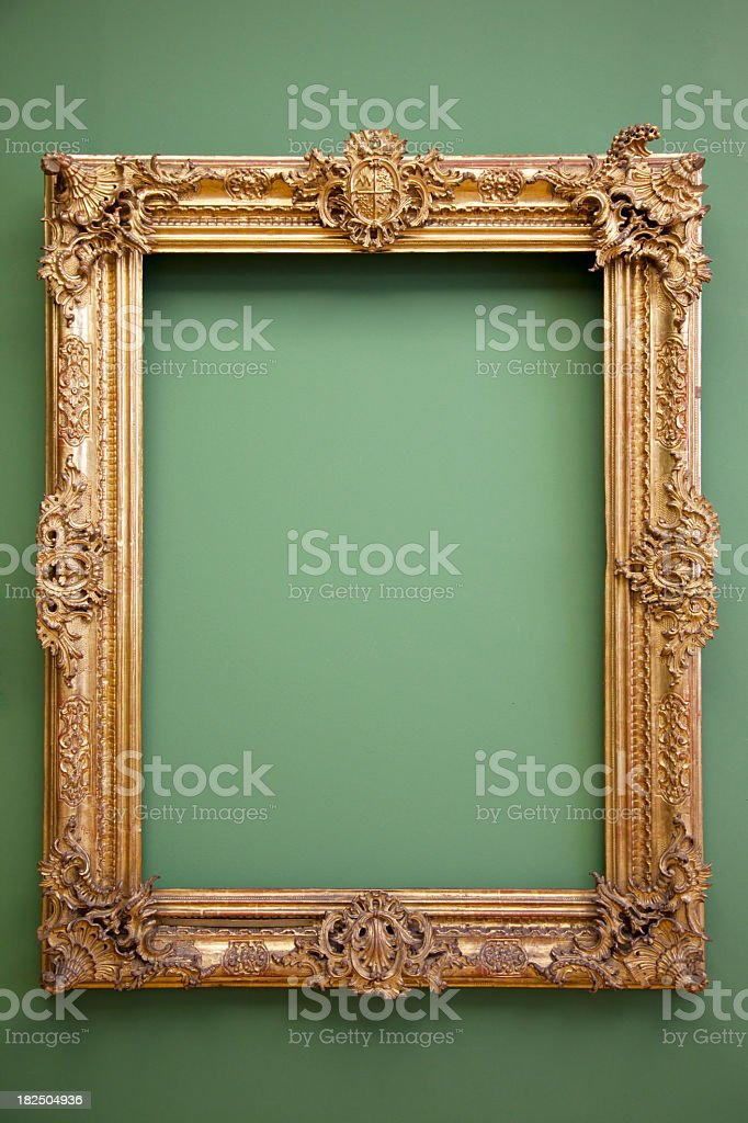 Empty golden baroque frame hanged in green wall royalty-free stock photo