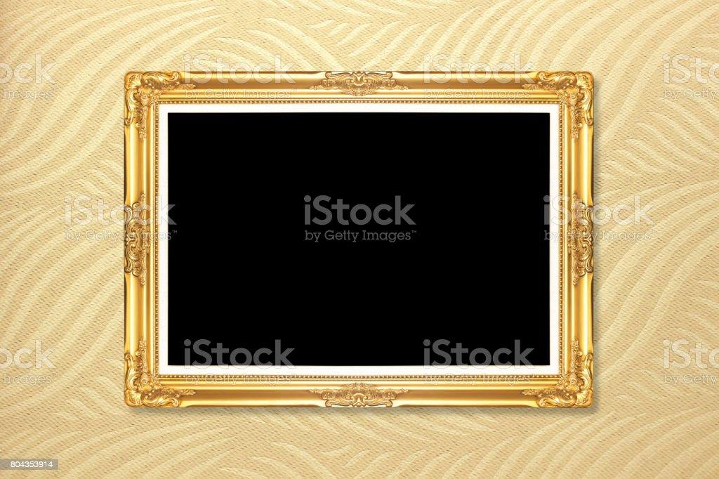 Empty golden vintage frame on wallpaper background stock photo