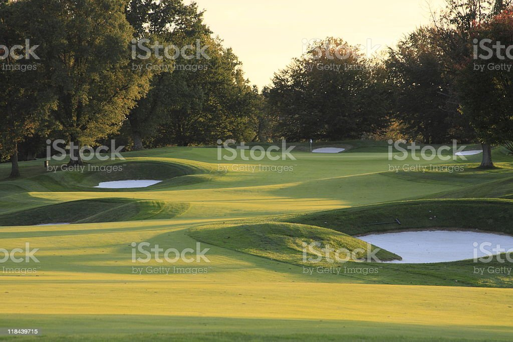 Empty golf course in autumn at sunset with sand bunkers stock photo