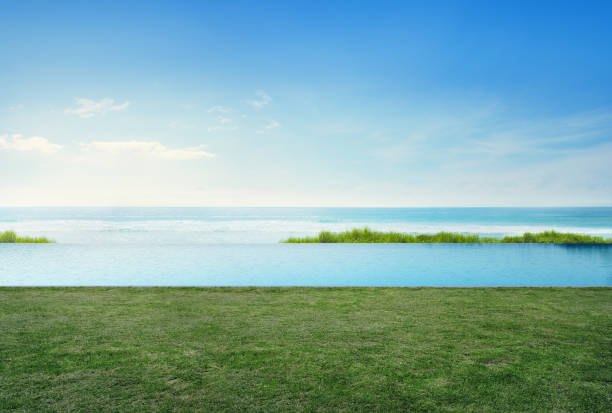 Empty grass floor deck in luxury beach house with blue sky background, Sea view terrace at vacation home or hotel stock photo