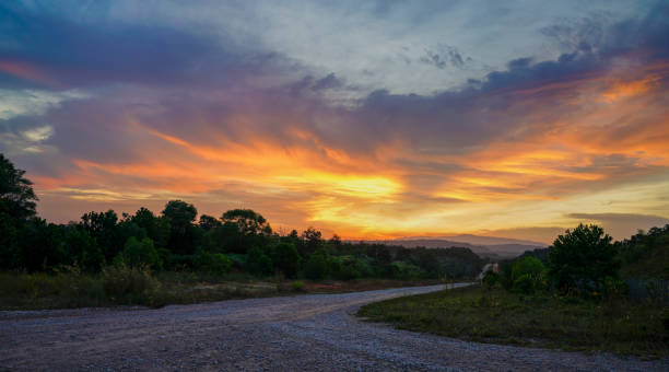 Empty gravel road against sunset stock photo