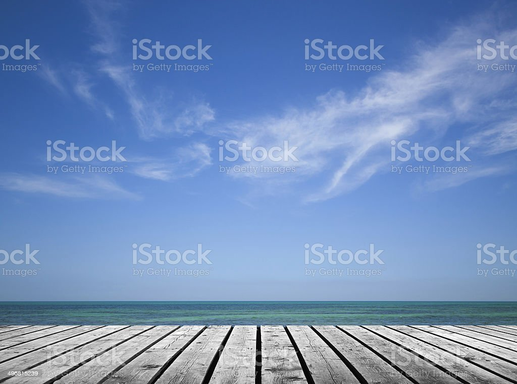 Empty gray wooden pier with sea and cloudy sky stock photo