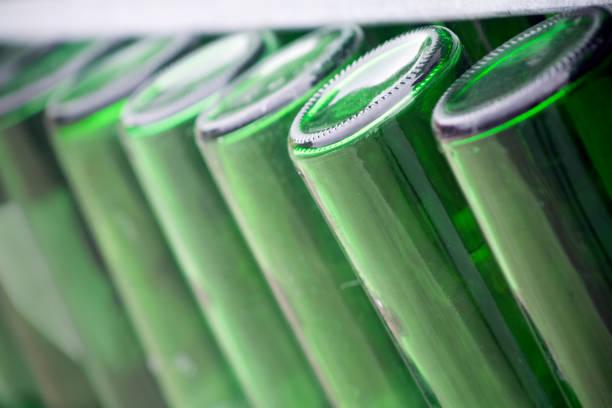 leere grüne flaschen hintereinander bereit für das recycling. - recycelte weinflaschen stock-fotos und bilder
